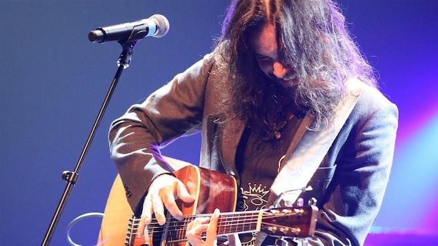 Le Franco-Manitobain Justin Lacroix chante sur scène en s'accompagnant à la guitare.
