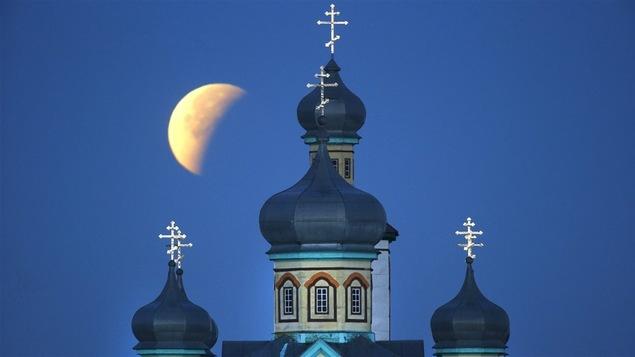 L'éclipse de lune au-dessus d'une église orthodoxe à Turets, au Bélarus.