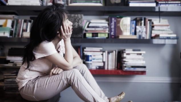 Kim Thuy réfléchit devant une bibliothèque