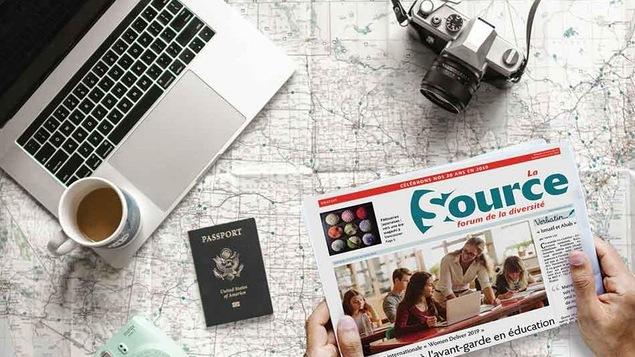 un journal, deux caméra, un laptop et un passeport posés sur une carte routière