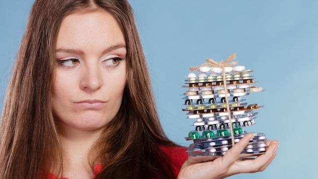 Femme tenant dans sa main de nombreux paquets qui contiennent des médicaments.