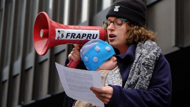 Une femme avec un bébé qui parle dans un porte-voix.