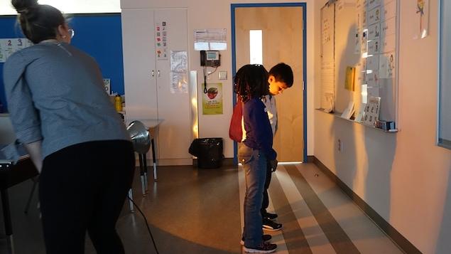 Des élèves regardent leurs ombres sur un tableau.