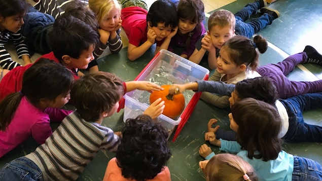 Des enfants testent la flottaison d'une citrouille.