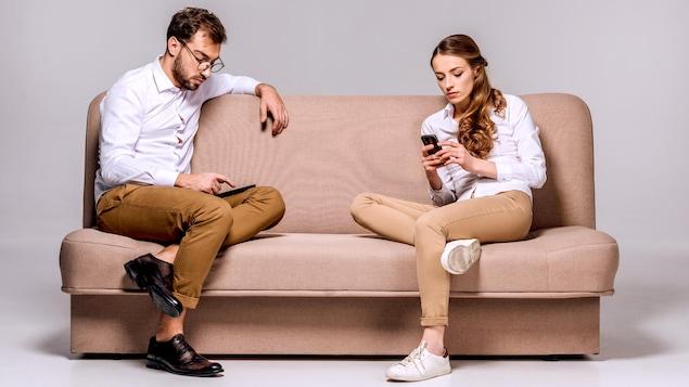 Jeune couple qui texte, assis sur un divan.