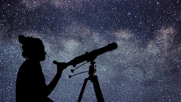 Une jeune fille regarde les étoiles avec un télescope.