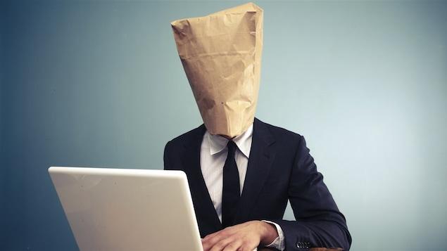 Un homme dont la tête est enfouie sous un sac de papier brun consulte l'Internet sur son ordinateur portable.