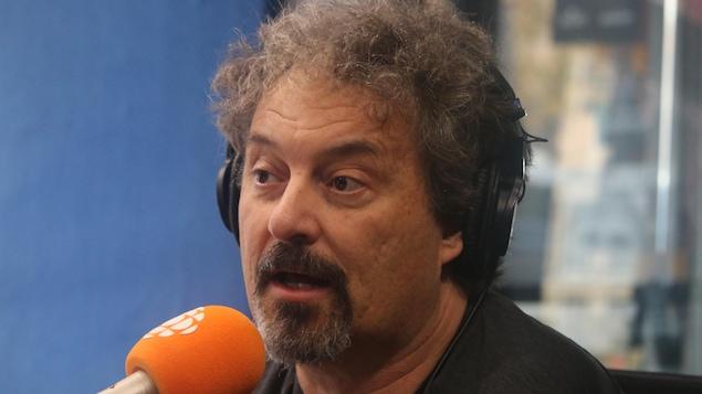 Un homme aux cheveux poivre et sel et portant un bouc parle au micro.