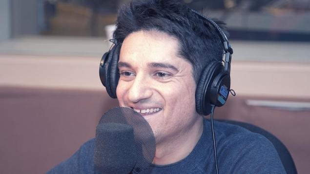 Assis derrière un micro, il porte des écouteurs.