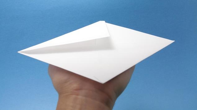 Une main tient une enveloppe devant un ciel bleu.