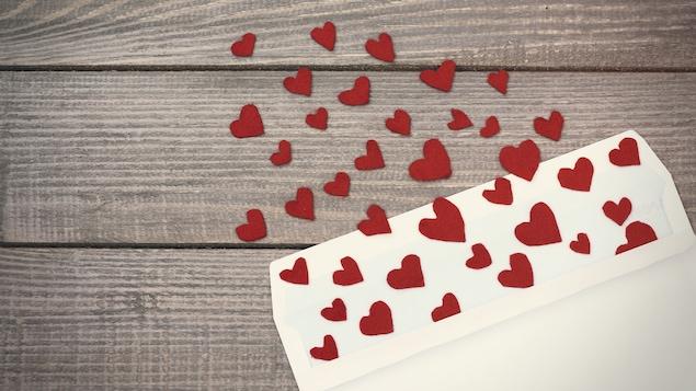 Des petits cœurs en papier rouge sortent d'une enveloppe blanche.