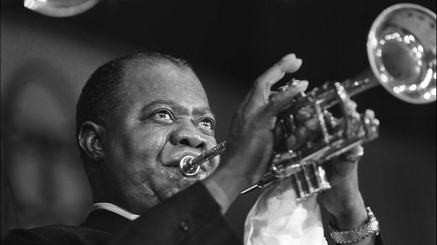Gros plan sur l'artiste soufflant dans sa trompette sous les feux de la scène.