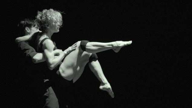 Louise Lecavalier, les jambes levées et pointées, est soulevée dans les airs par son partenaire de danse.