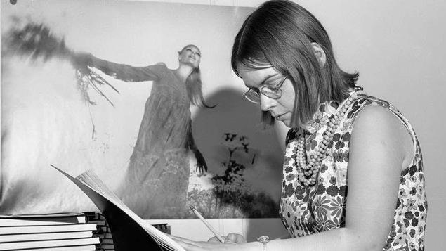 Photo en noir et blanc montrant une jeune femme en train d'écrire dans un grand livre.