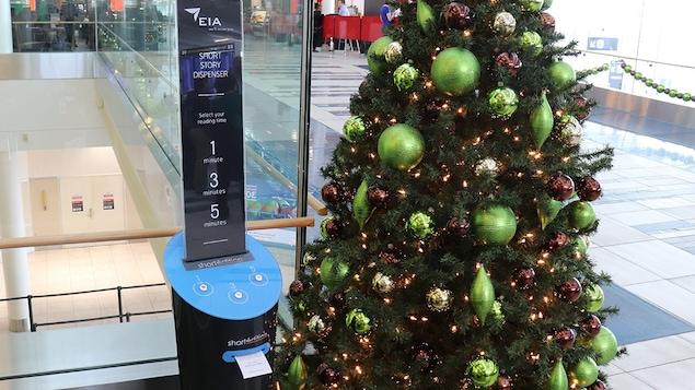 Une petite machine qui imprime des histoires sur du papier à côté d'un sapin de Noël dans un aéroport