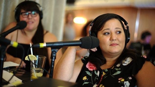 Julie Artacho, à gauche, et Manal Drissi, qui regardent vers leur gauche avec des écouteurs sur la tête.