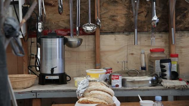 Une cuisine rudimentaire dans laquelle on voit plusieurs louche accrochées au mur, des boîtes de conserve sur un comptoir et un panier de pain plat.
