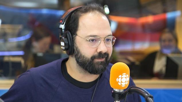 Des lunettes devant les yeux, il porte des écouteurs et est assis derrière un micro.