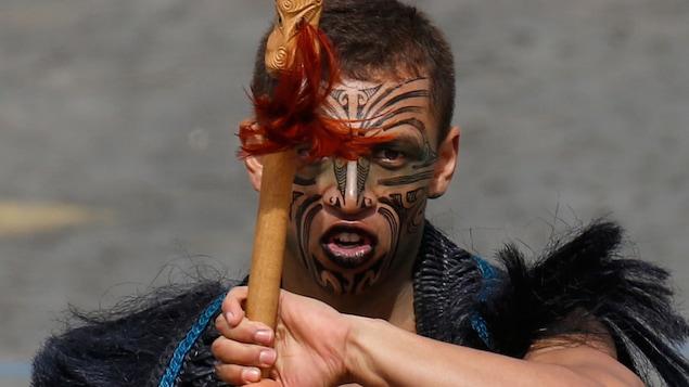 Un homme au visage tatoué tient un bâton de bois ornomenté dans ses mains.