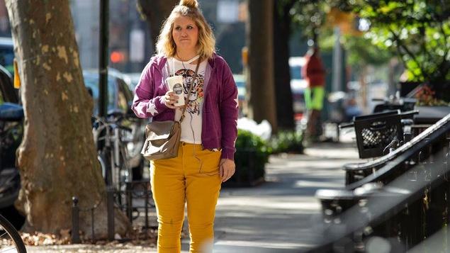 Une femme tient un café sur le trottoir de la rue.