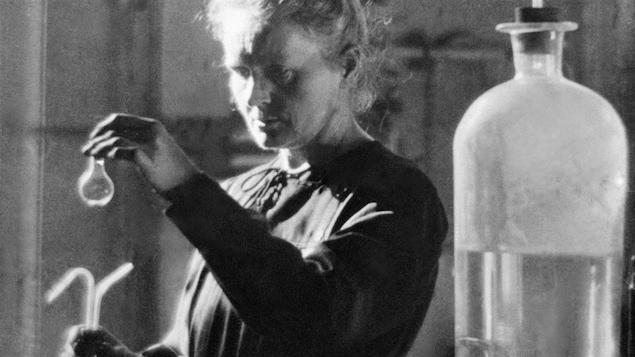 Marie Curie tient une fiole dans ses mains.