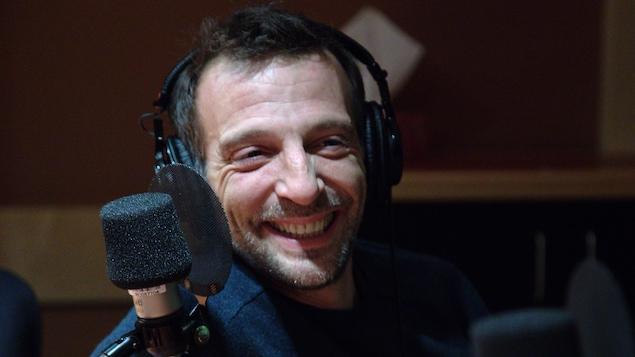 Mathieu Kassovitz, des écouteurs sur la tête, est assis derrière un micro.