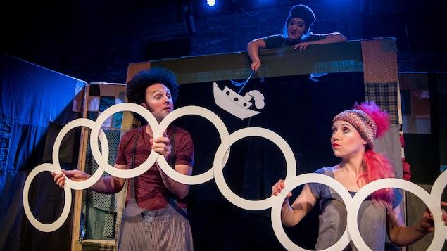 Trois comédiens manipulent des anneaux et la marionnette d'un navire devant une scène improvisée.
