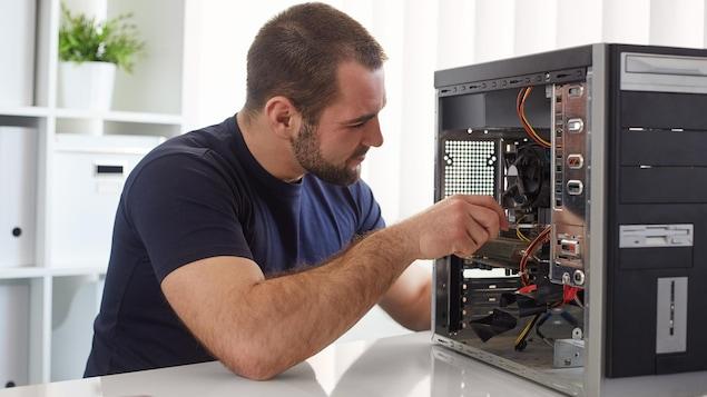 Un homme répare le disque dur de son ordinateur.