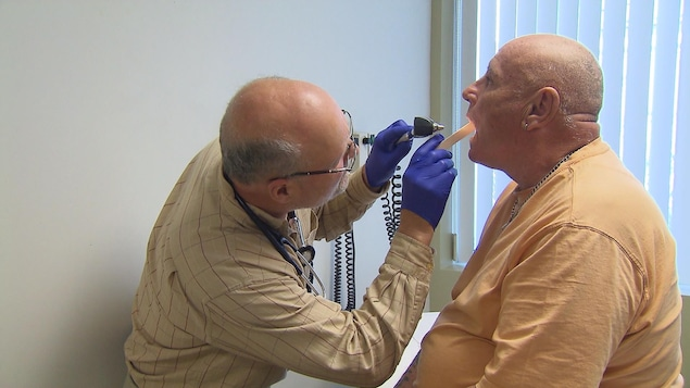 Un médecin ausculte un patient.