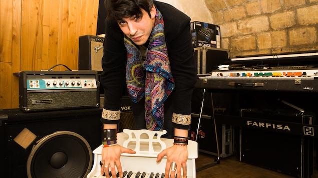 L'artiste entouré d'instruments et d'amplificateurs de son.