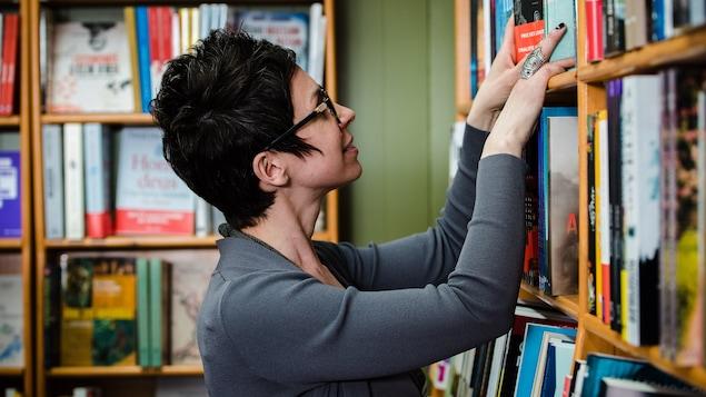 On voit une femme qui se trouve dans une bibliothèque. Elle manipule quelques livres dans une étagère.