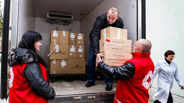 Dans un camion ouvert, un homme donne des boîtes à un autre au sol, tandis qu'une femme les regarde.