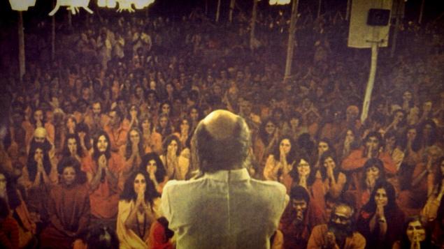 Une scène montre Bhagwan Rajneesh devant des disciples dans le documentaire <em>Wild Wild Country</em>.