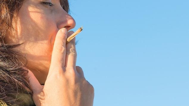 Une femme vue de profil fume un joint sous un ciel bleu.