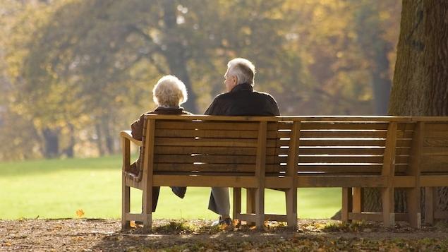 Un couple de baby-boomers sur un banc de parc.