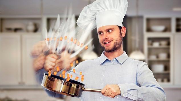 Un chef cuisiner coupe les aliments si vite que ses mouvements sont flous.