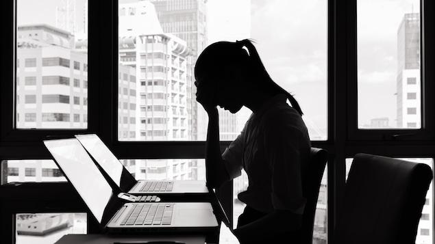 Profil d'une femme déprimée à son clavier d'ordinateur.