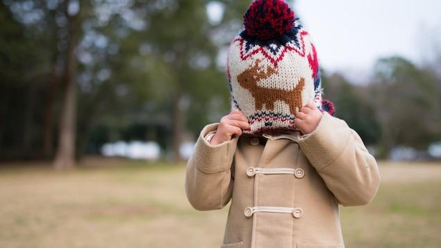 Une petite fille très timide tire les rebords de sa tuque pour cacher son visage.