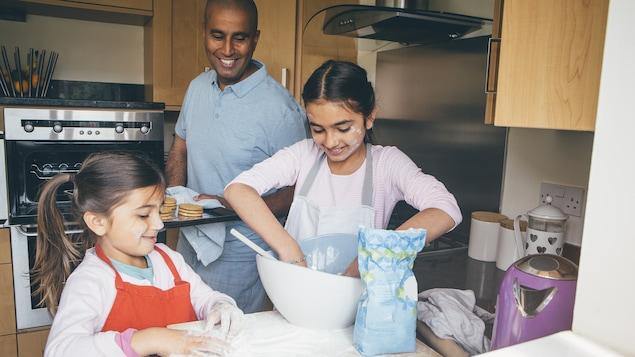 Deux petites filles ont les mains dans la farine au comptoir de cuisine, sous le regard de leur père souriant.