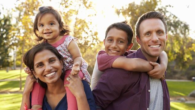 Une mère et un père tenant chacun en enfant sur leurs épaules