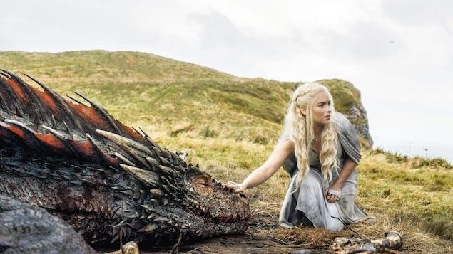 L'actrice Emilia Clarke touche un dragon une scène de la série <i>Game of Thrones</i>.