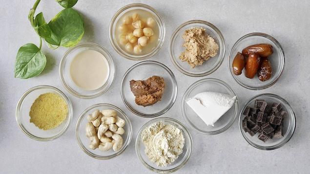 Dix petits plats, posés sur une table grise, contenant chacun une petite quantité d'ingrédients.