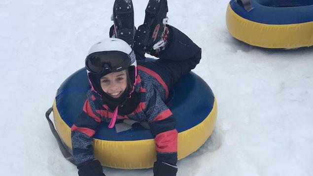Une jeune fille sur un tube pour glisser sourit à la caméra.