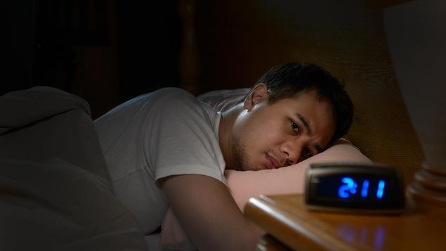 Un homme souffrant d'insomnie regarde mélancoliquement son réveil depuis son lit.