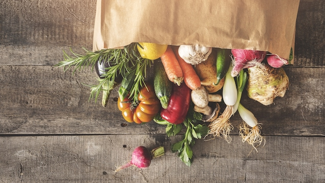 Des légumes frais sortant d'un sac renversé sur une table.