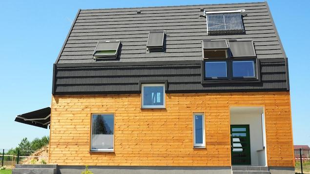 Une maison moderne en bois, avec un toit de couleur foncée et un panneau solaire.