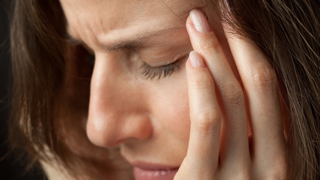Une femme se tient les tempes, comme si elle souffrait d'un mal de tête.