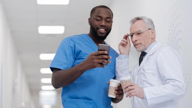 Un jeune homme montre à un homme plus âgé quelque chose sur son téléphone intelligent.