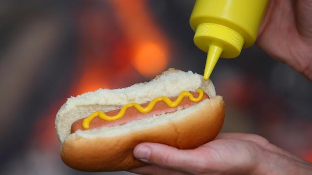 Une personne met de la moutarde dans un hot dog.