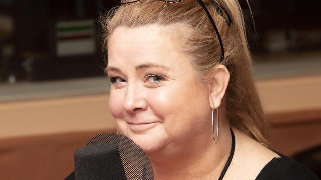 Une femme devant un micro regarde la caméra en souriant légèrement.